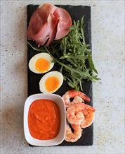 Spanish Tapas Plate of Egg, Prosciutto and Shrimp with Romesco and Arugula
